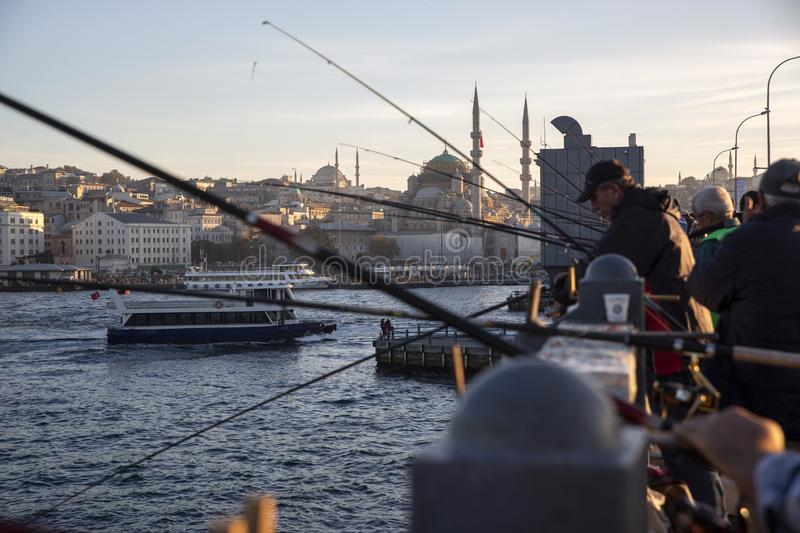 Istanbul Galata Bridge in Karakoy districts in daylight with fishing people walking and city skyline royalty free stock image