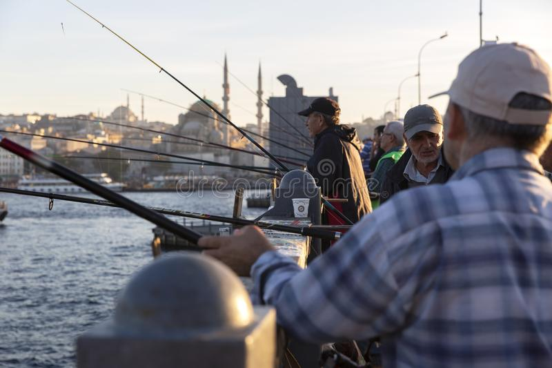 Istanbul Galata Bridge in Karakoy districts in daylight with fishing people walking and city skyline.  stock photography