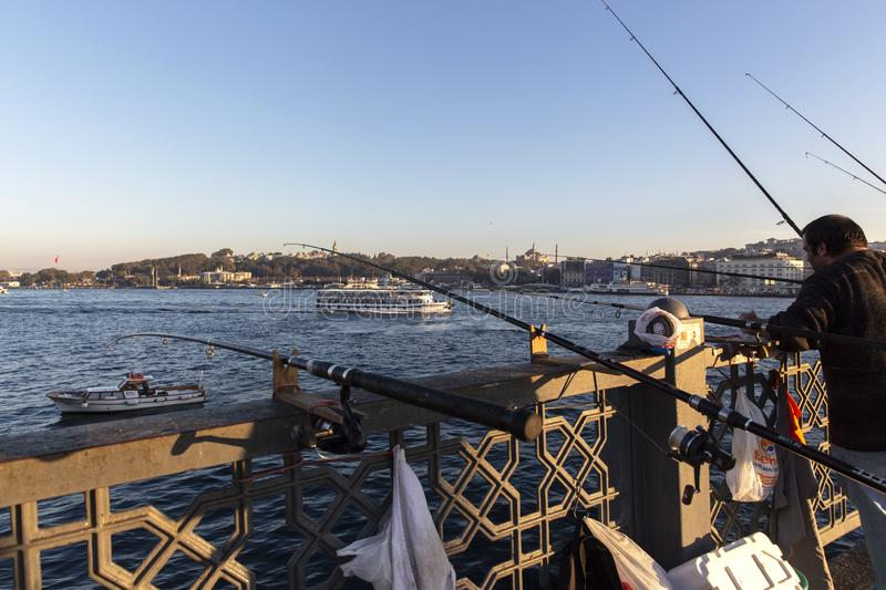 Istanbul Galata Bridge in Karakoy districts in daylight with fishing people walking and city skyline.  royalty free stock photos