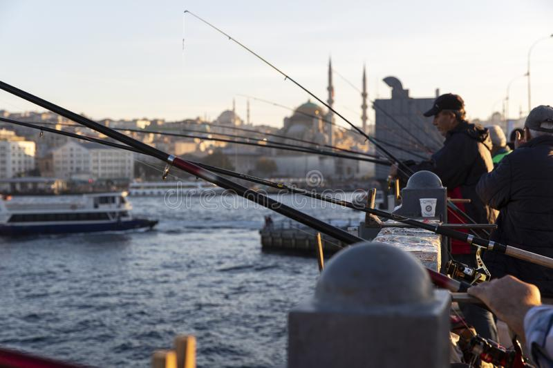 Istanbul Galata Bridge in Karakoy districts in daylight with fishing people walking and city skyline.  royalty free stock photo