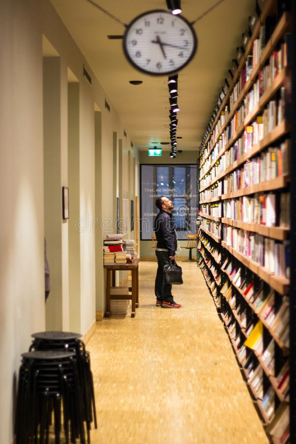 Istanbul, Istiklal Street / Turkey 9.5.2019: Salt Beyoglu Art Center, Men Trying to Pick a Book. Stand and Looking Up to Somewhere stock photography