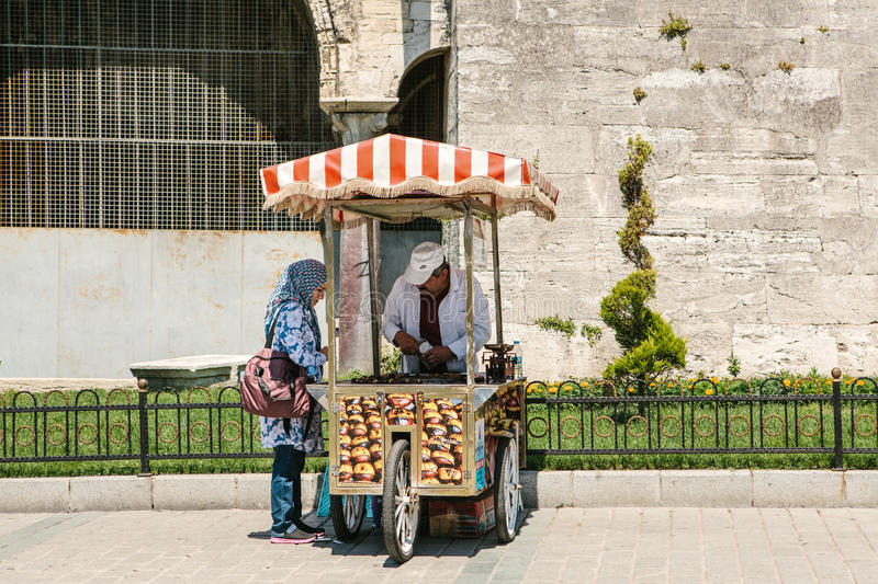 Istanbul, June 15, 2017: Pretty muslim woman in hijab purchasing roasted chestnuts from friendly street vendor royalty free stock photography