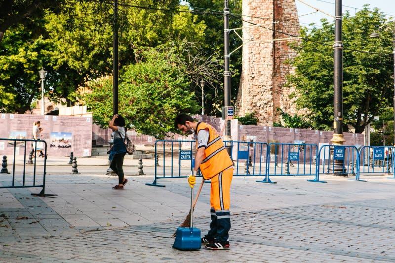Istanbul Juni 15, 2017: dörrvakt i ljus orange likformig som sopar tegelplattan på gatan i det Sultanahmet området arkivbilder