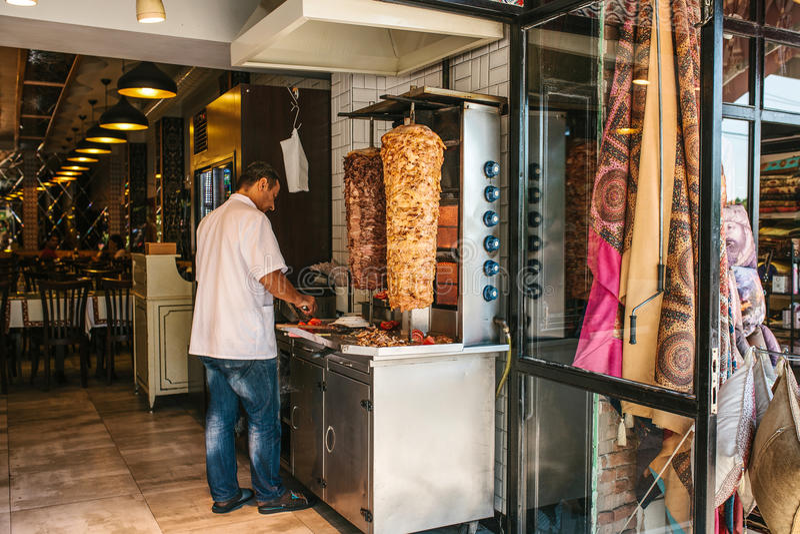 Istanbul Juni 15, 2017: den turkiska kocken är laga mat och skiva gyroskopdelar i restaurangen Skjutit i en studio royaltyfri bild