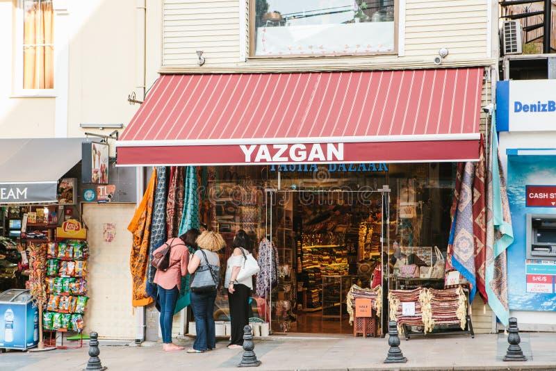Istanbul, am 15. Juni 2017: Drei weibliche Touristen wählen zusammen Waren und Geschenke in einem traditionellen Straßenteppichsp stockfotografie