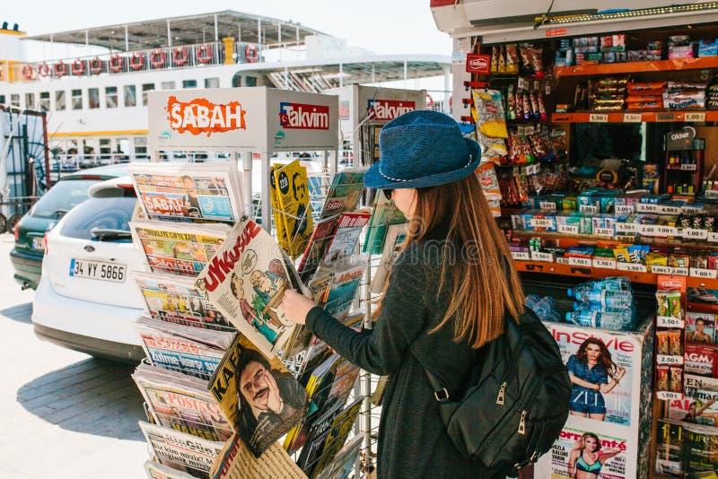 Istanbul, le 17 juin 2017 : La jeune belle fille dans un chapeau avec un sac à dos achète un magazine ou un journal dans une pres photographie stock