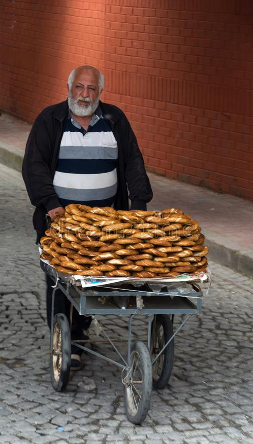 ISTANBUL-MAY 20 :一个老人卖在推车2015年5月20日的芝麻百吉卷伊斯坦布尔,土耳其 图库摄影