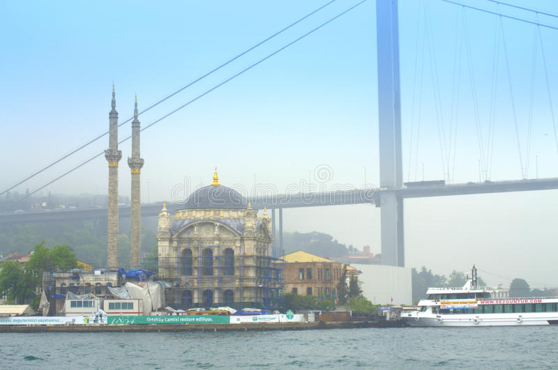 Istanbul mosque and Bosphorus bridge. Ortakoy Mosque and part of First Bosphorus Bridge connecting Europe and Asia continents at fogy rainy day,Istanbul,Turkey stock image