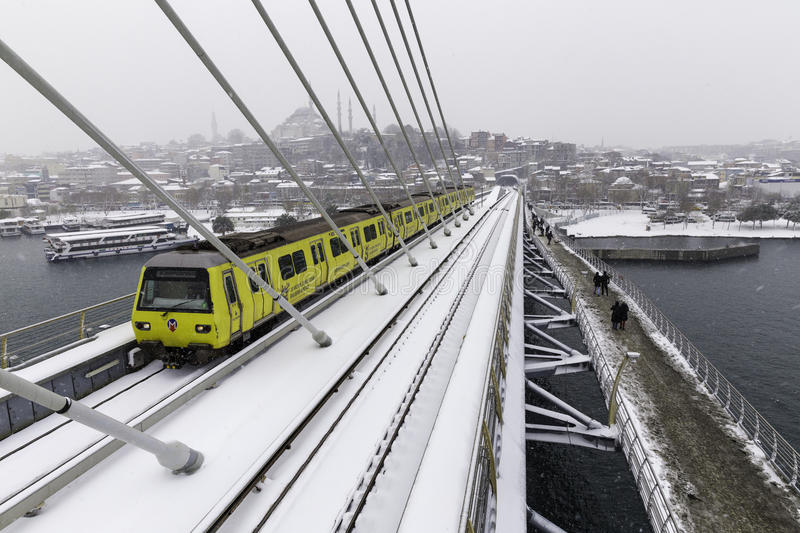 Istanbul subway metro train passing and people walking on the Golden Horn Metro Bridge. On a snowy day near Halic in Istanbul, Turkey stock photo