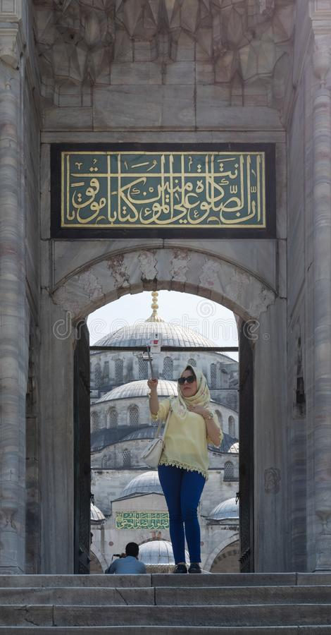 Female tourist taking a selfie photo in front of one of the entrances of the Blue Mosque, Istanbul, Turkey. Istanbul, Turkey - April 16 2017: Female tourist stock photo
