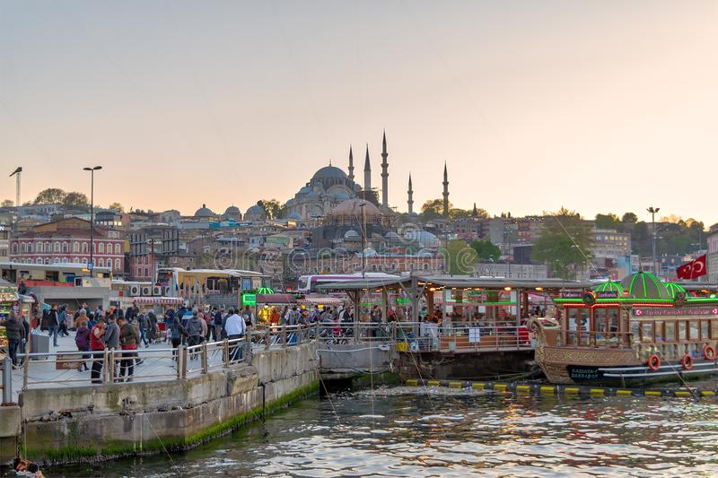 Fish sandwiches bobbing boats at Eminonu district with Rustem Pasha and Suleymaniye Mosques in the background, Istanbul, Turkey. Istanbul, Turkey - April 25 stock images