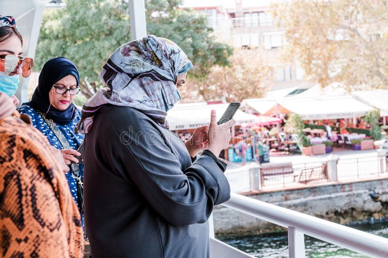 ISTANBUL, TURKEY - August 29, 2018: Muslim woman taking pictures on mobile phone royalty free stock images