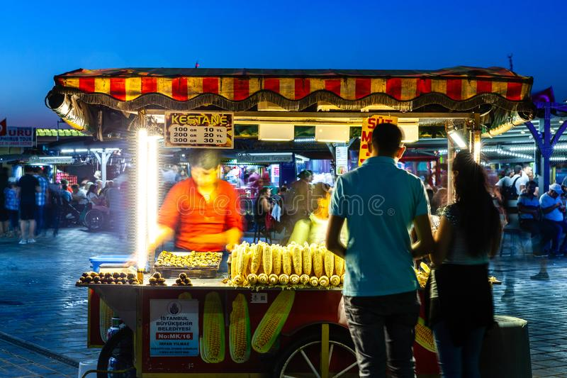 Street food vendor sells corn cobs and roasted chestnuts on the. ISTANBUL, TURKEY - AUGUST 14: Street food vendor sells corn cobs and roasted chestnuts on the royalty free stock photos