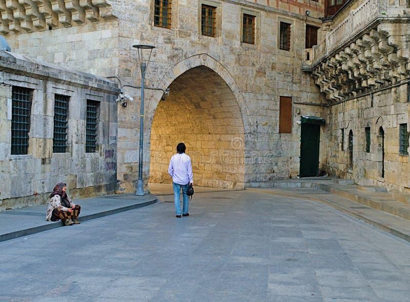 Businessman walking past a beggar woman stock photos