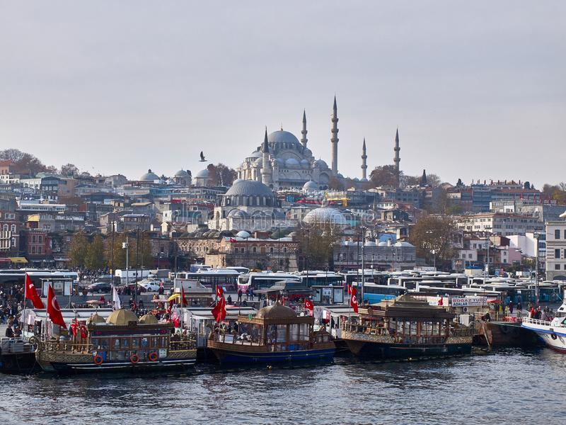 Istanbul, Turkey - December 2019. Floating fast food boats at Golden Horn bay opposite Suleymaniye Mosque at background royalty free stock photos