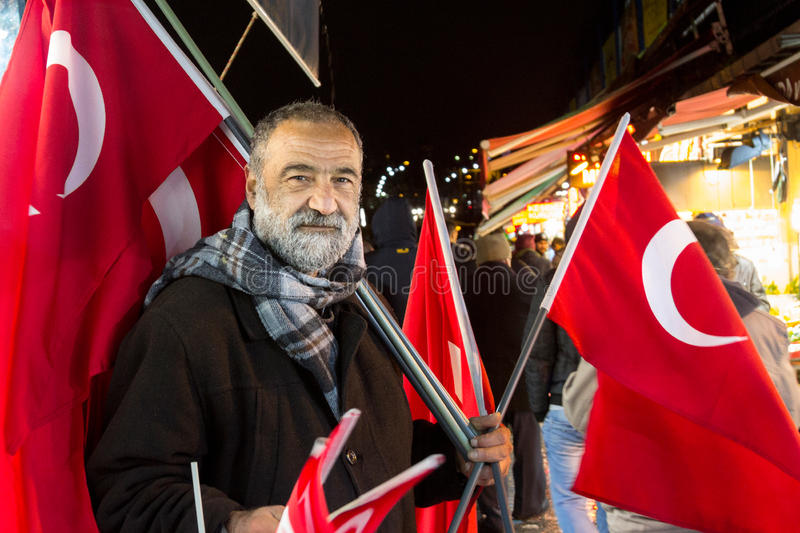 ISTANBUL, TURKEY - DECEMBER 30, 2015 : Old man selling Turkish flags on the European part of Istanbul royalty free stock photos