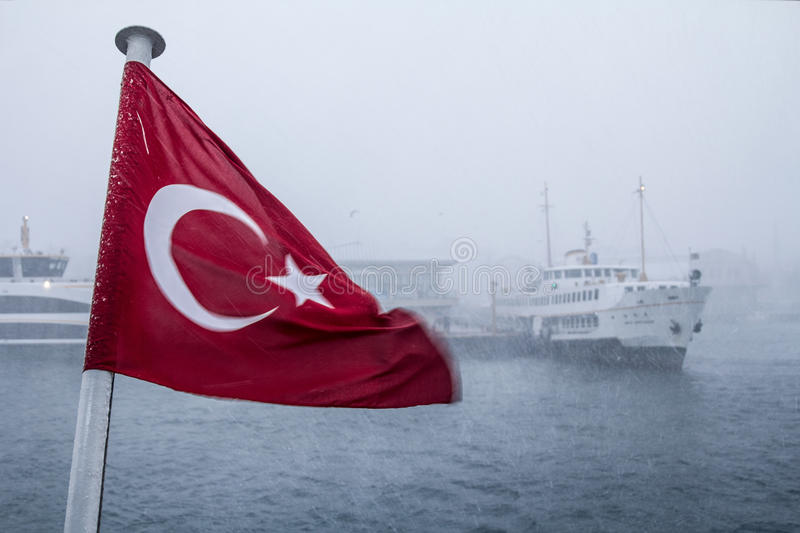 ISTANBUL, TURKEY - DECEMBER 30, 2015: Turkish flag during a snowstorm, a Europe-Asia ferryboat can be seen in the background. Picture of ships on Europe Asia stock image