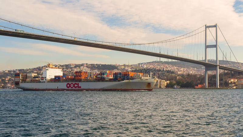 Loaded container ship owned by Orient Overseas Container Line passing Bosphorus bridge, Istanbul. Istanbul, Turkey - January 20 2013: Loaded container ship owned stock photography