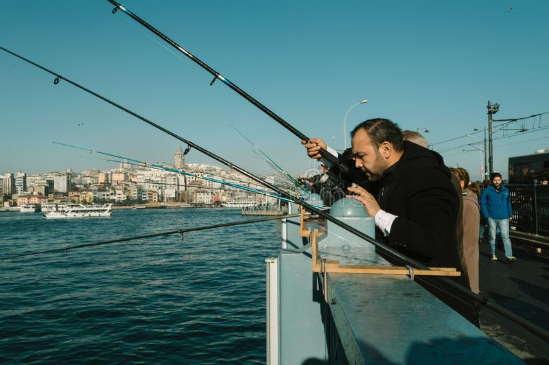 Istanbul, Turkey - January 06, 2018: Local fishermen fishing on Galata Bridge to relax and enjoy their hobby in Istanbul royalty free stock image