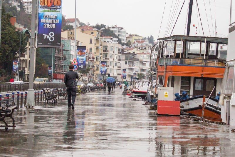 Istanbul Turkey January 31 2019: A man walking down the docks on rainy day. Orange transportation boat is moored on the docks. stock photo