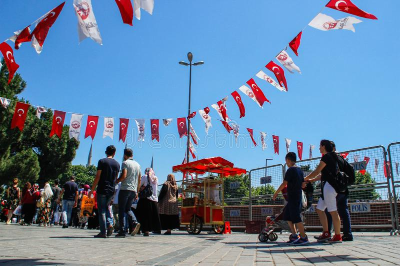 Kadikoy city center with a crowd of people and Turkish flags hanging on the ropes. Istanbul, Turkey - June 26, 2017: Kadikoy city center with a crowd of people royalty free stock images