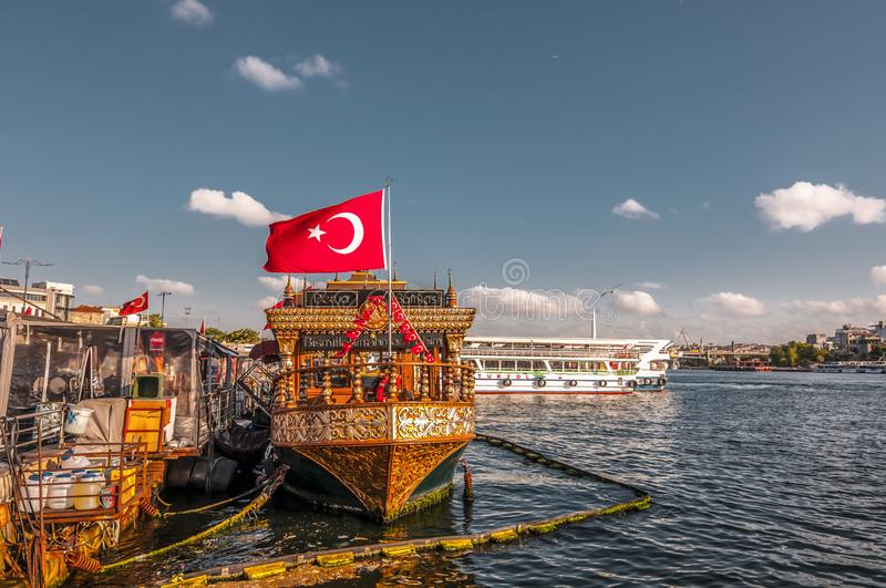 Fisnd and bread boats in Eminonu, Istanbul. Istanbul, Turkey - June 27, 2019: Traditional fish-and-bread boats along Eminonu coast on the Golden Horn against royalty free stock images