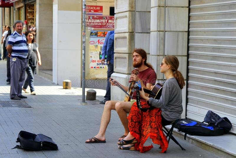 Two street musicians are playing guitar and violin in the center of city. ISTANBUL, TURKEY - JUNE 22, 2015: Two street musicians are playing guitar and violin stock photography