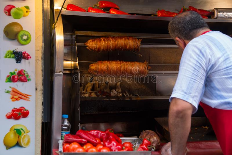 Istanbul, Turkey: A man is cooking meat on the street. Street vendor roast meat on a spit. Traditional popular dish royalty free stock photo