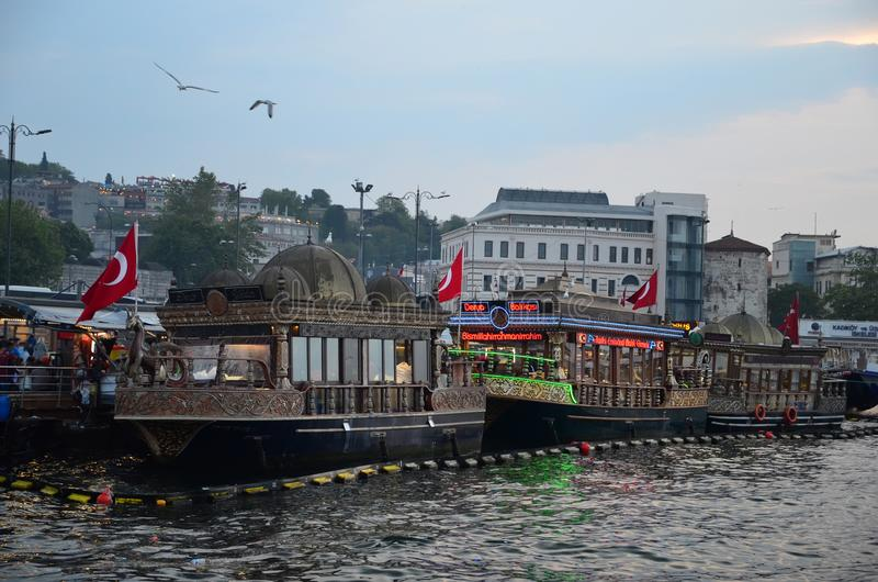 ISTANBUL/TURKEY - MAY 10, 2018: Beautiful boats on Bosfor embankment in Istanbul from the Galata Bridge. Gulls in the sky. Dusk time royalty free stock photos