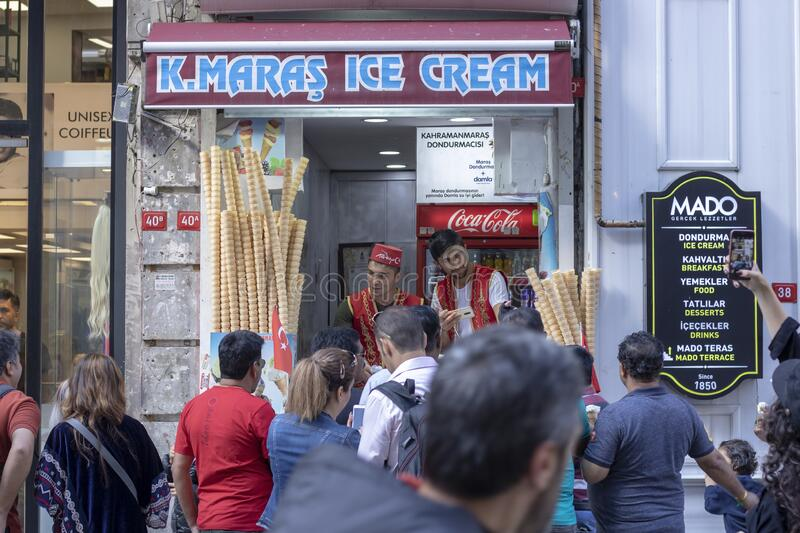 Street ice cream vendor, dressed in traditional Turkish costume gives ice cream to the girl stock image