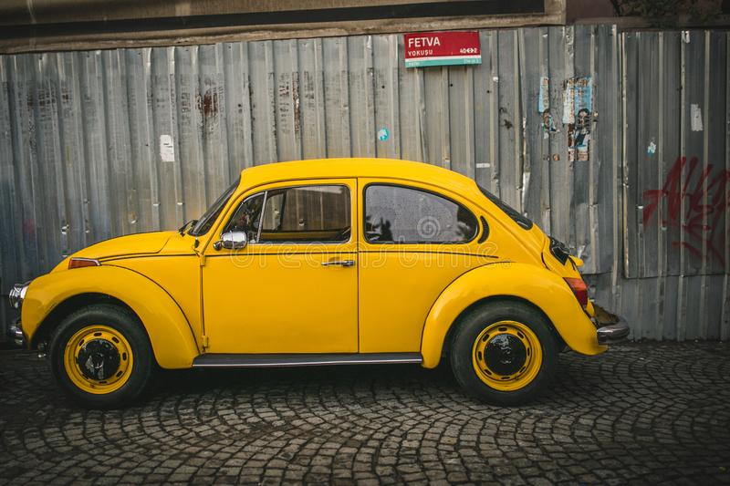 yellow vintage volkswagen kafer near fence in Istanbul, Turkey royalty free stock image