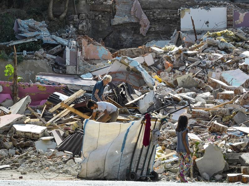 Istanbul, TURKEY, September 20, 2018. An elderly, a young men and girl collect garbage on the ruins of a destroyed house.  stock photo