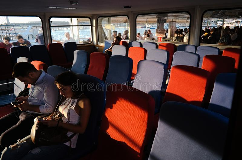 Passenger travel on ferry soft chairs on the boat. Istanbul, Turkey - September, 2018: Passenger travel on ferry from Eminonu to Kadikoy. Evening sunset light stock photos
