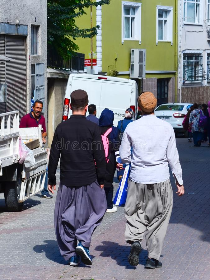 Istanbul, TURKEY, September 20, 2018: Two Muslim men in traditional dress go shopping on the street of the old town stock photos