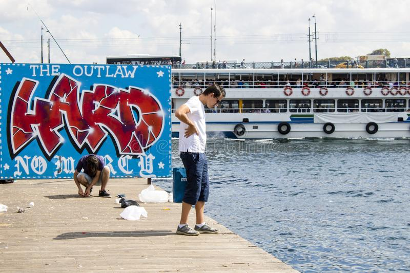 Istanbul, Turkey - September-14,2019: The young man watching the beach on the pier and the garbage on the ground behind. Graffiti stock image