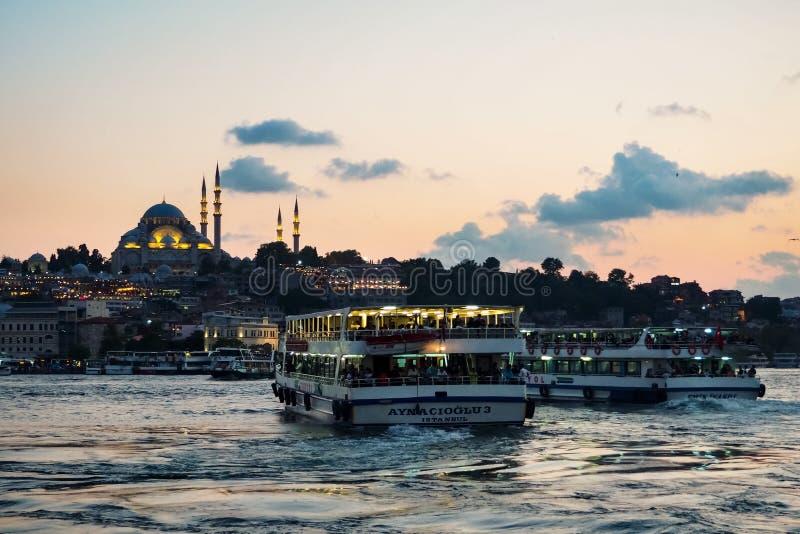 ISTANBUL TURKIET - AUGUSTI 21, 2018: sikt från den Galata bron som förbiser det guld- hornet med färjor och den Suleymaniye moské arkivfoto