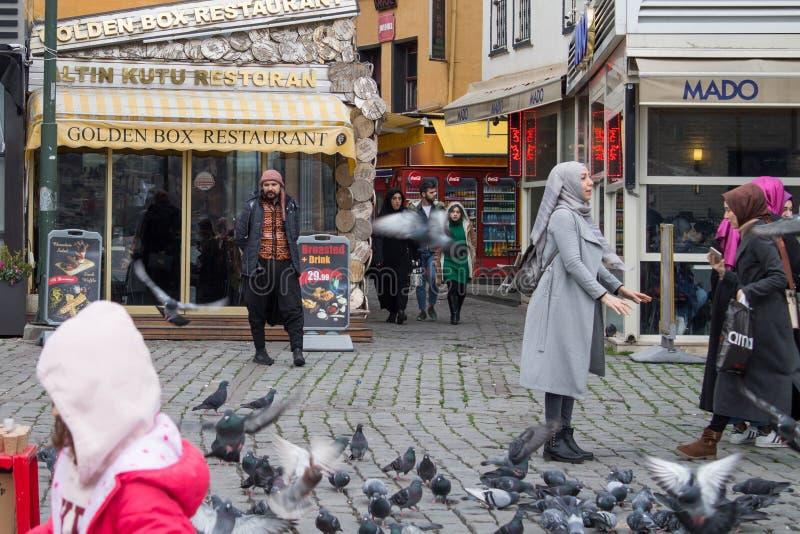 Istanbul Turkiet - Januari 31 2019: En man annonserar restaurangen, medan folket matar och fångar duvor arkivfoto