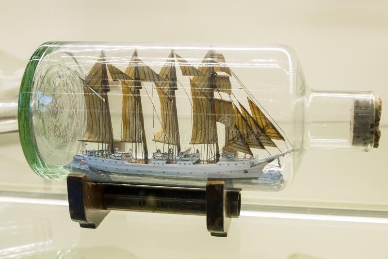 Istanbul Turkiet, 23 mars 2019: Det miniatyrhögväxta skeppet med seglar riggat i en klar glasflaska som visas på ett litet fotografering för bildbyråer