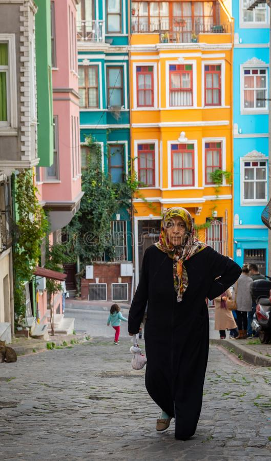 Istanbul Turkiet 10-November-2018 En syriansk flyktingkvinna i Fener-Balat med färgrika hus bakom arkivbild