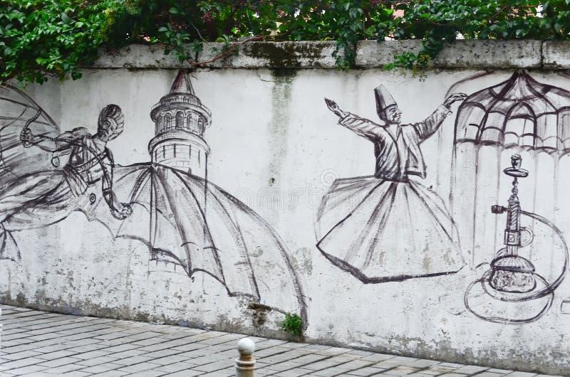 Istanbul TURKIET, September 25, 2018 för grafittigata för konst färgrik räknad vägg Dansen av dervischerna och flygmannen royaltyfri fotografi