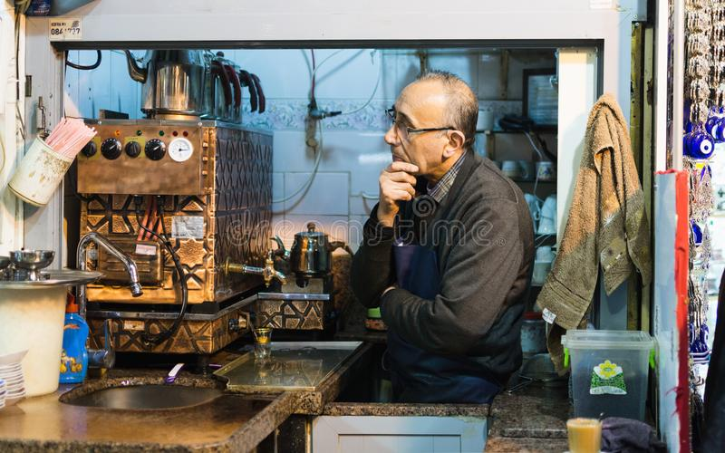 ISTANBUL, TURQUIE - AVRIL 2015 : fabricant de thé regardant hors de son kiosque le bazar grand photographie stock