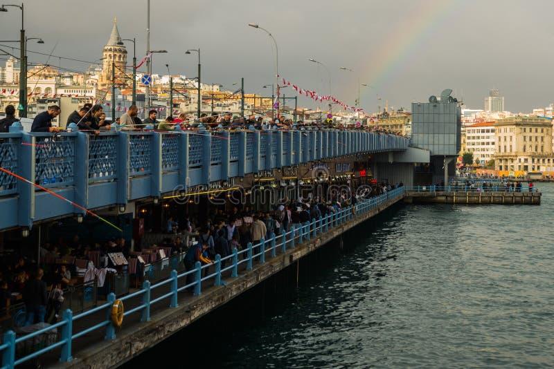 Istanbul, Turquie : les gens pêchant du pont de Galata par temps nuageux En bas restaurants avec le poisson frais Tour de Galata photographie stock