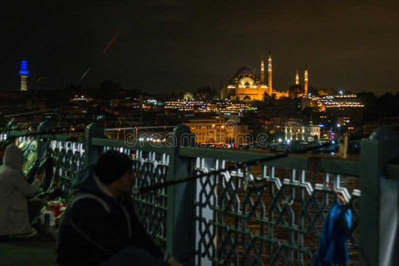 Istanbul, Turquie : les pêcheurs de nuit pêchent sur le pont de Galata dans la distance à la mosquée bleue avec des lumières pêch photo libre de droits