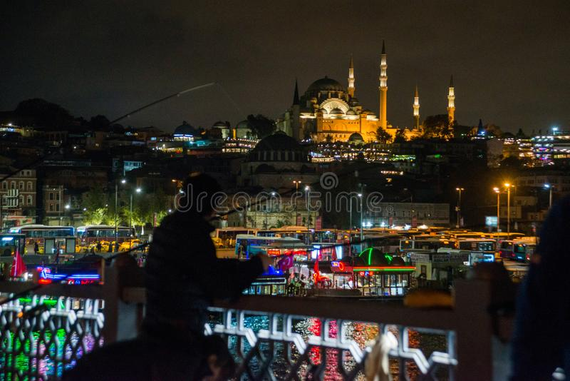 Istanbul, Turquie : les pêcheurs de nuit pêchent sur le pont de Galata dans la distance à la mosquée de Suleymaniye avec des lumi photographie stock libre de droits