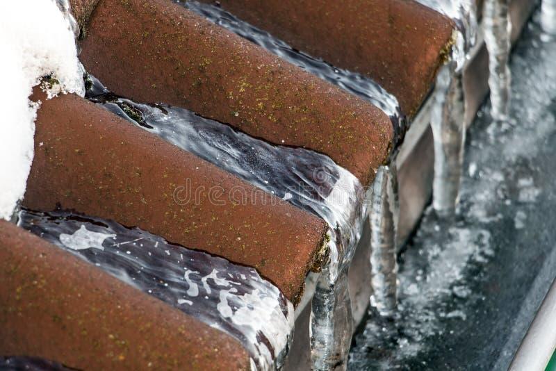 Istappar på ett snöig tak royaltyfria foton