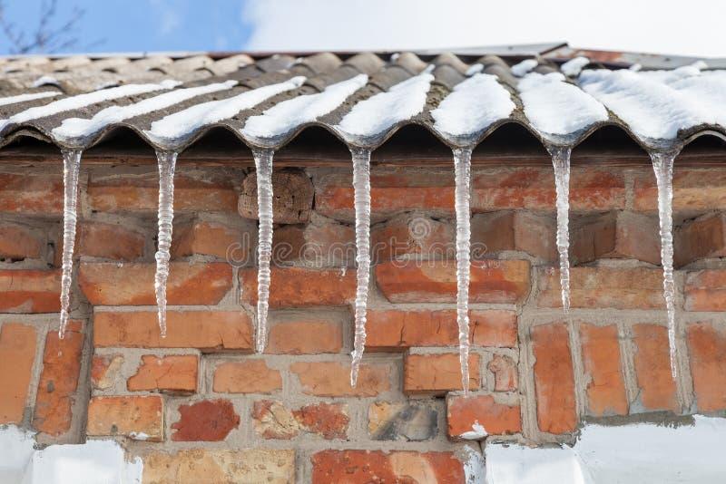 Istappar på taket av huset royaltyfri foto