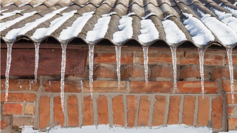 Istappar på taket av huset royaltyfria bilder
