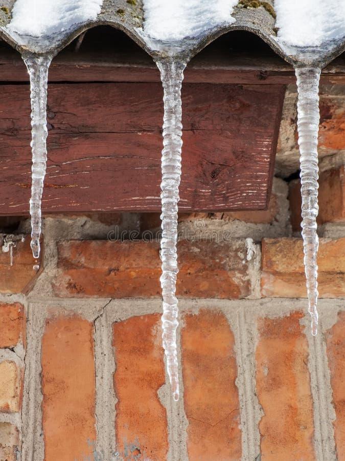 Istappar på taket av huset arkivbilder
