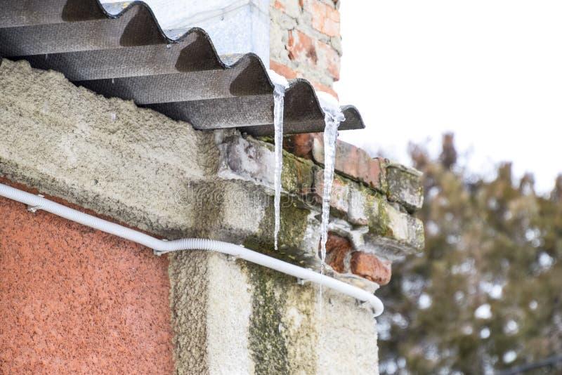Istappar på taklägga Otryggt tak Frysa vatten i istappen royaltyfri foto