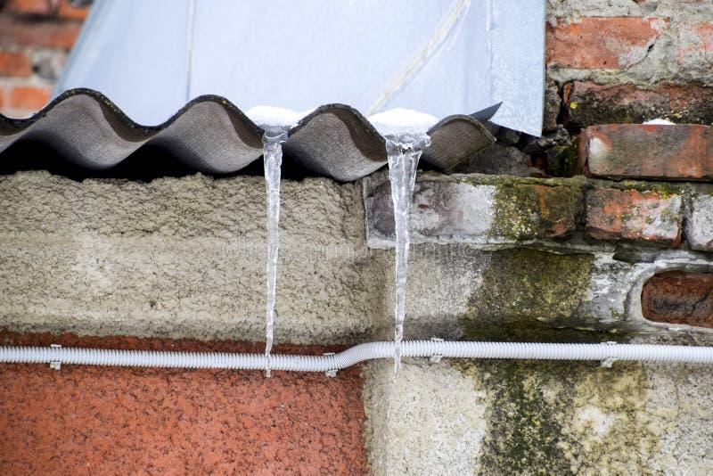 Istappar på taklägga Otryggt tak Frysa vatten i istappen royaltyfria foton